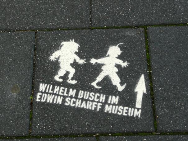 Graffiti auf Gehweg - 'Wilhelm Busch im Edwin Scharff Museum'